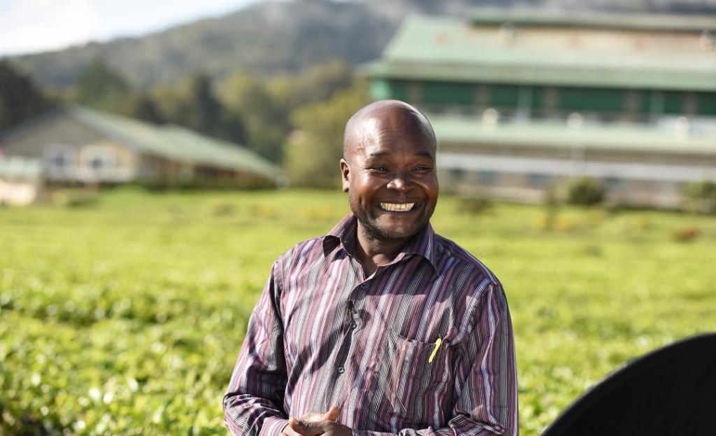 Tea farmer Patrick Kaberia smiling in tea field